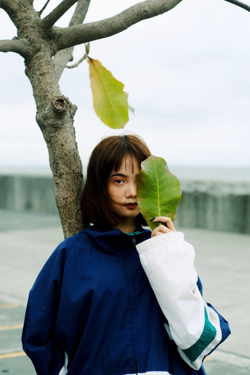 photo of woman in blue and white jacket leaning on tree while holding a large green leaf in front her eye